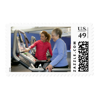 A personal trainer helps a senior woman on a postage