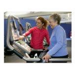 A personal trainer helps a senior woman on a postcard
