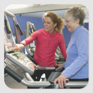 A personal trainer helps a senior woman on a square sticker