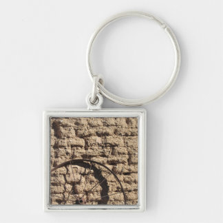 A Photo of a Wagonwheel on a Brick Wall Keychain
