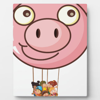 A pig balloon carrying a basket with kids photo plaques