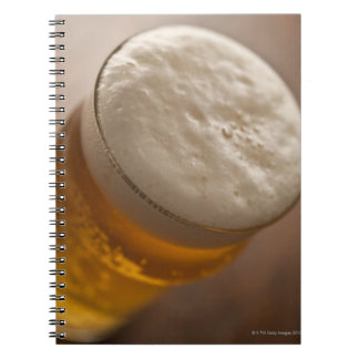 A pint of lager, back lir shallow focus rustic note books