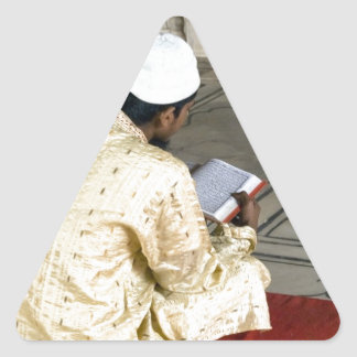 A pious devotee reading the Quran Triangle Sticker