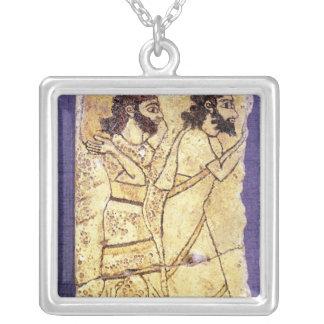 A plaque depicting two men walking square pendant necklace