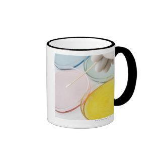 A plastic gloved hand sampling from petrie ringer mug