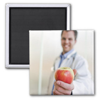 A portrait of a doctor holding a apple. magnet