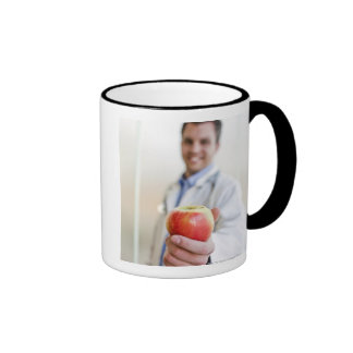 A portrait of a doctor holding a apple. ringer mug