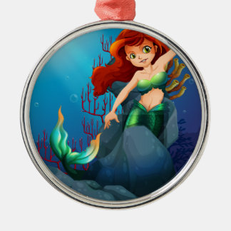 A pretty mermaid trapped with the big rocks under round metal christmas ornament