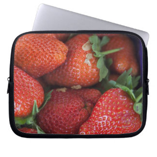 a punnet of ripe fresh strawberries for sale in laptop sleeve