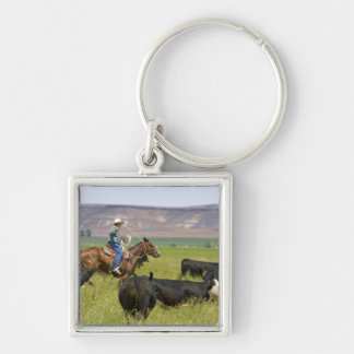 A rancher on horseback during a cattle roundup 2 keychain