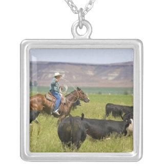A rancher on horseback during a cattle roundup 2 silver plated necklace