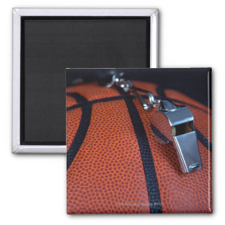 A referee's whistle rests on top of a 2 inch square magnet