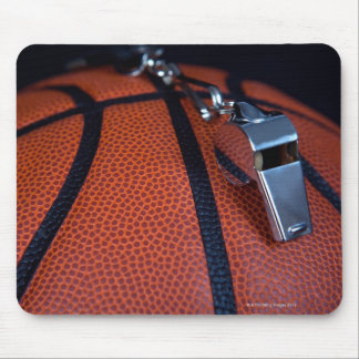 A referee's whistle rests on top of a mouse pad