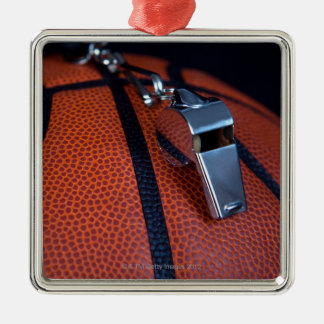 A referee's whistle rests on top of a square metal christmas ornament