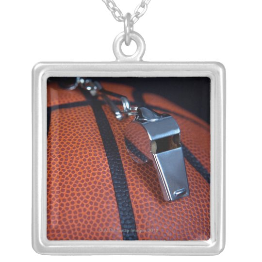 A referee's whistle rests on top of a silver plated necklace