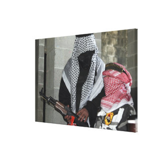 A role-playing enemy aggressor arms a dummy gallery wrapped canvas