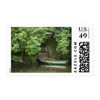 A Row Boat Roped At Some Stairs Along The Shore Postage