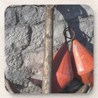 A rusty anchor and two orange conical buoy beverage coaster