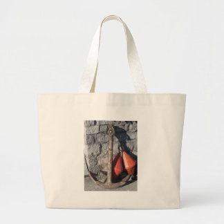 A rusty anchor and two orange conical buoy large tote bag