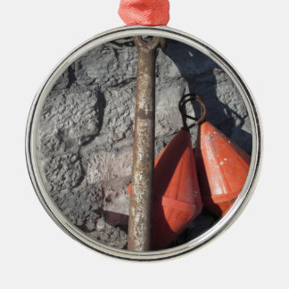 A rusty anchor and two orange conical buoy metal ornament