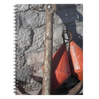A rusty anchor and two orange conical buoy notebook