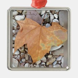 a rusty leaf on pebbles metal ornament