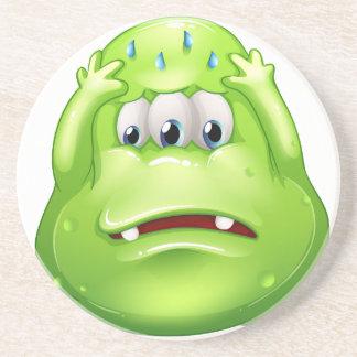 A sad greenslime monster drink coaster
