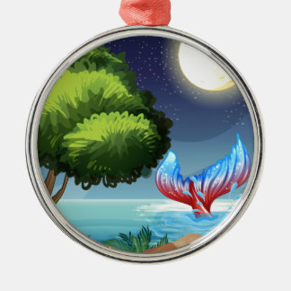 A sea with a tail of a mermaid round metal christmas ornament