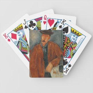 A seated man leaning on a table bicycle playing cards