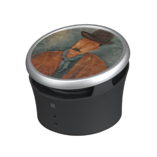 A seated man leaning on a table bluetooth speaker