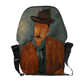 A seated man leaning on a table courier bag