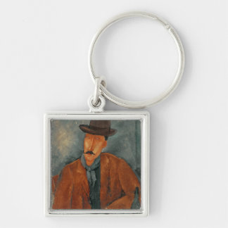 A seated man leaning on a table keychain