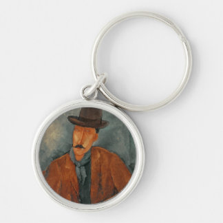 A seated man leaning on a table Silver-Colored round keychain