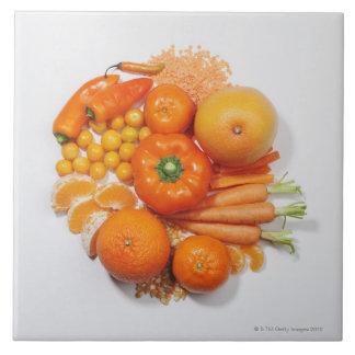 A selection of orange fruits & vegetables. large square tile