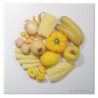 A selection of yellow fruits & vegetables. large square tile