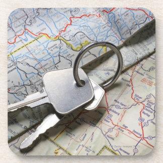 A set of car keys on a pile of road maps. beverage coaster
