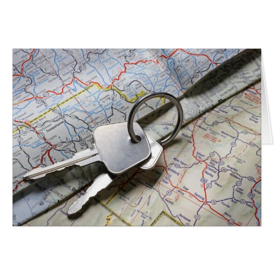 A set of car keys on a pile of road maps. card