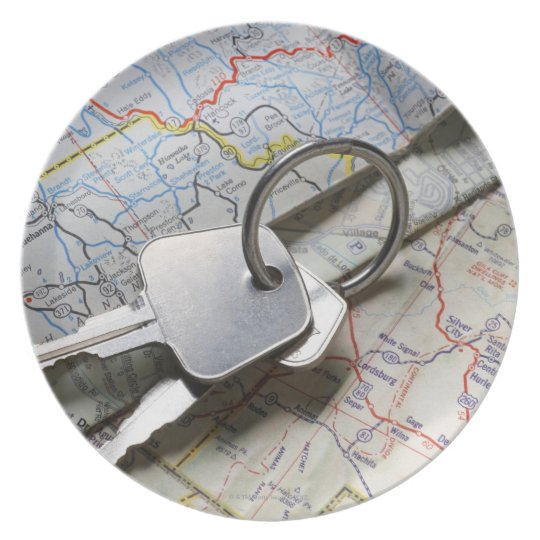 A set of car keys on a pile of road maps. dinner plate