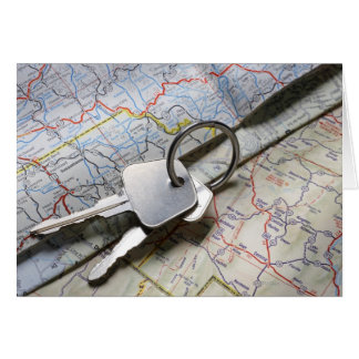 A set of car keys on a pile of road maps. greeting card