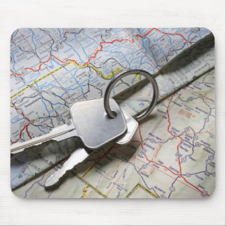 A set of car keys on a pile of road maps. mouse pad