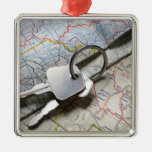 A set of car keys on a pile of road maps. square metal christmas ornament