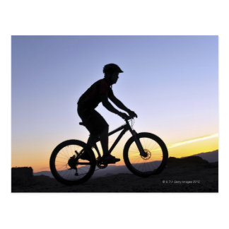 A silhouette of a mountain biker at sunset on postcard