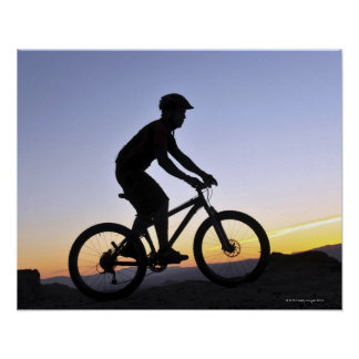 A silhouette of a mountain biker at sunset on poster