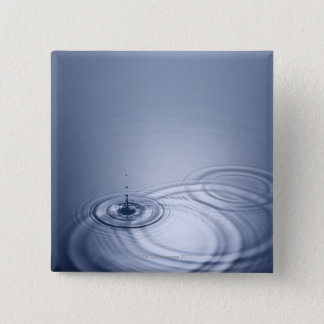 A single droplet of water falling into a calm pinback button