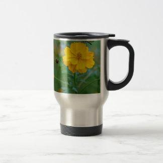 A small dragon fly sitting on a yellow flower mug