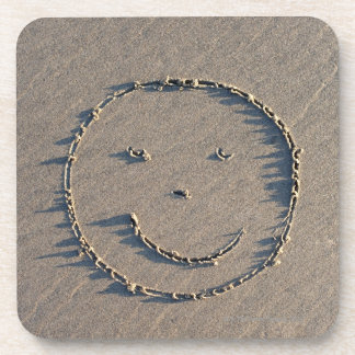 A smiley face drawn in sand. coaster