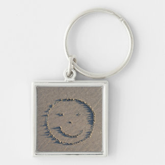 A smiley face drawn in sand. keychain