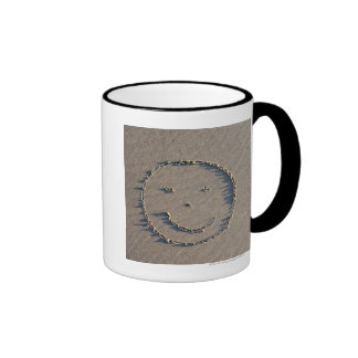 A smiley face drawn in sand. ringer coffee mug