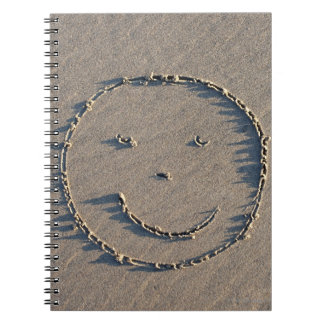A smiley face drawn in sand. spiral notebook