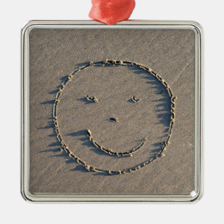 A smiley face drawn in sand. square metal christmas ornament